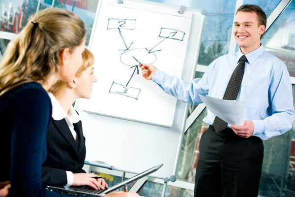 Image of confident man explaining his business strategy pointing to board to coworkers